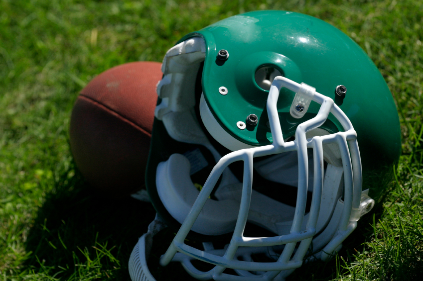 Close-up of a green football helmet on grass