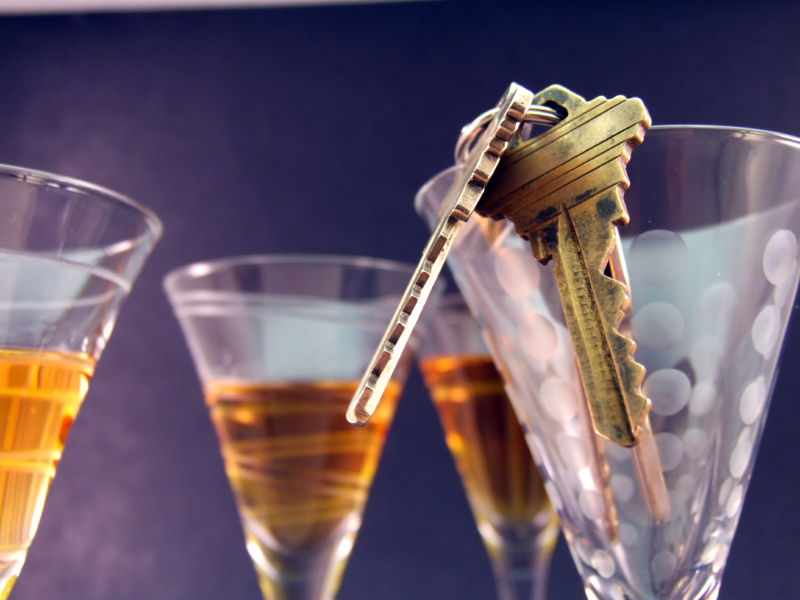 keys hanging on top of glasses with alcohol